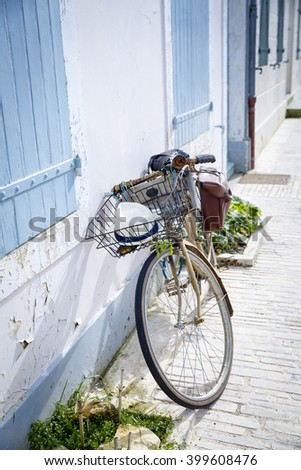 Seaside holidays house with blue wooden shutters with a bike in front - stock photo