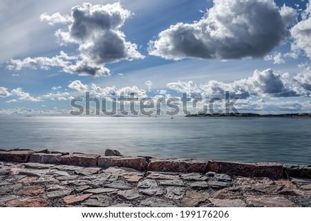 Seaside landscape with cloudy sky, scandinavian nature. - stock photo