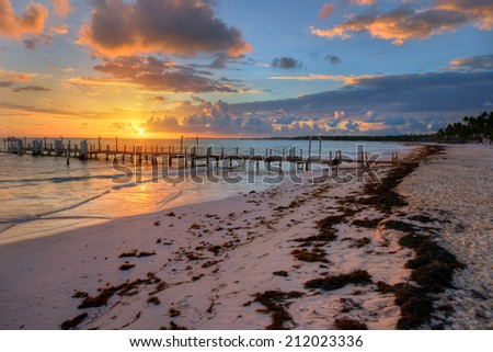 Seaside pier sunrise with dramatic clouds, seaweeds, and bright colors - stock photo