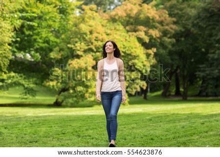 season and people concept - beautiful happy young woman walking in summer park