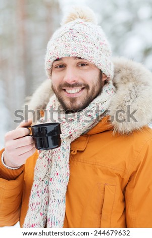 season, christmas, drinks and people concept - happy smiling young man with cup drinking hot tea in winter forest - stock photo