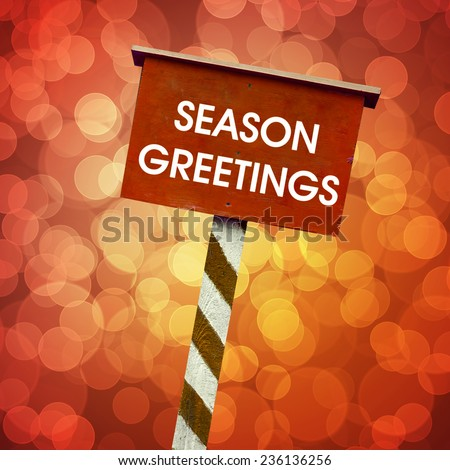 Season greetings board written on red background with defocused lights - stock photo