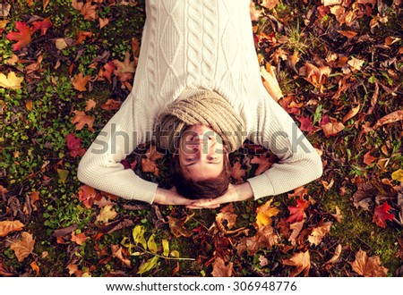 season, happiness and people concept - smiling young man lying on ground or grass and fallen leaves in autumn park - stock photo