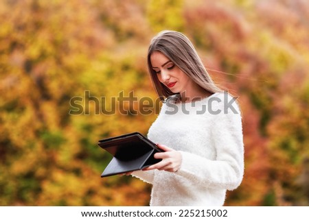 season, technology and people concept - young woman with tablet pc computer in autumn park - stock photo