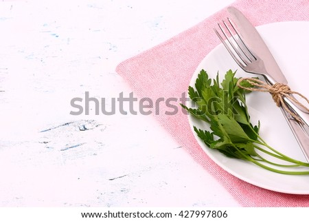 Seasonal old white wooden table with cutlery - stock photo