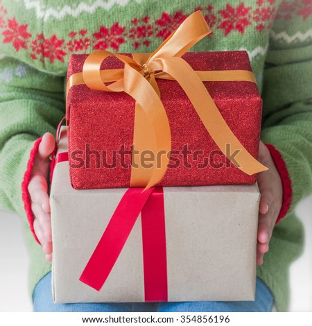 Seasonal present gift boxes w/ gold ribbon in child kid hand wearing colorful red green knit sweater (shallow focus) Holiday winter season celebration: Happy new year & Merry christmas 2016 boxing day - stock photo
