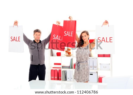 Seasonal sale: happy couple holding shopping bags inside of a store.