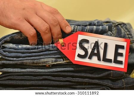 Seasonal sale. Man's hand touches pile of clothes, shopping, black friday, columbus day sale, labor day sale - stock photo