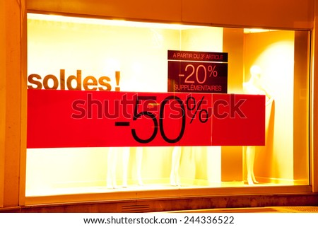 Seasonal sales sign on the window of French clothing store - stock photo