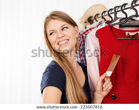 Seasonal sales. Young female customer buying clothes in shopping mall. Happy smiling Caucasian woman holding price tag indoors in store. - stock photo