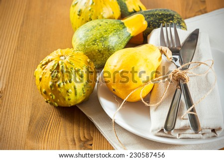 Seasonal table setting with small pumpkins on wooden table - stock photo