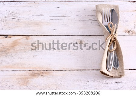 Seasonal white wooden table with cutlery - stock photo