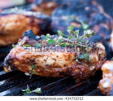 Seasoned and marinated chicken thighs topped with fresh thyme being grilled on iron grates over charcoal - stock photo