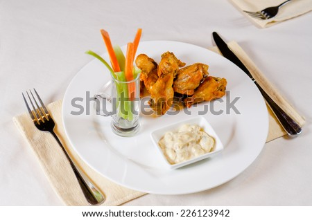 Seasoned grilled chicken wings with a glass filled with fresh carrot and celery crudites served with a creamy savory sauce for dipping - stock photo