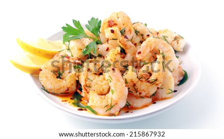 Seasoned savory pink prawns or shrimp tails grilled in fresh diced herbs and butter and served with slices of fresh lemon for a gourmet seafood starter - stock photo