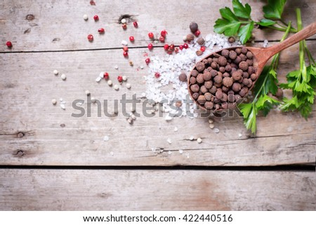 Seasoning for cooking. Allspice pepper in wooden spoon and sea salt, red pepper and herb parsley  on aged wooden background. Food ingredient. Selective focus. Place for text. Flat lay. Top view. - stock photo