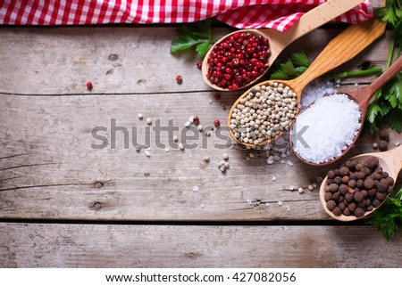 Seasoning for cooking. Red, white and allspice pepper and sea salt in wooden spoon on aged wooden background. Food ingredient. Selective focus. Place for text. Flat lay. Top view.  - stock photo