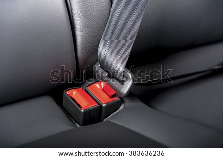 seat belt on a black leather chair with red lock
