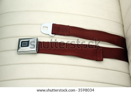 Seat belt, unbuckled, on leather seat of classic car - stock photo