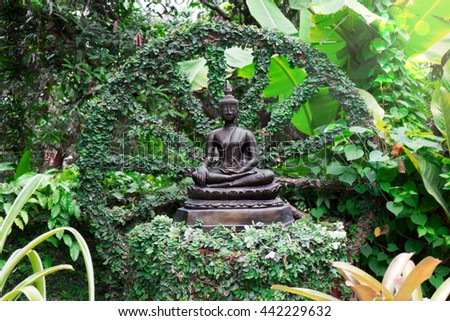 Seated Buddha statue with green leaf background, Buddha statue at beautiful nature garden - stock photo