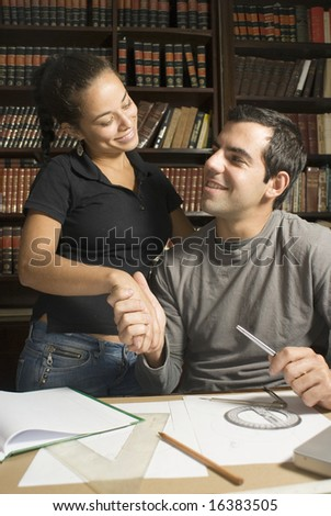 Seated man shakes hand of standing woman. They are studying and smiling at each other. Vertically framed photo. - stock photo