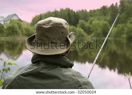 Seated senior man fishing off a shoreline - stock photo