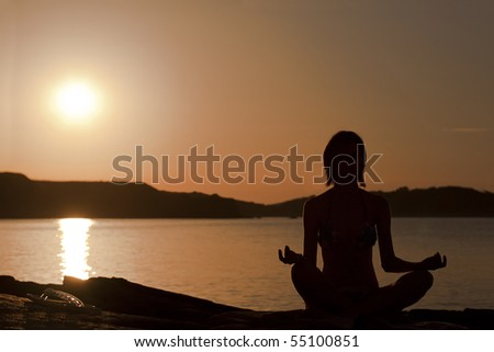 Seated yoga pose. Sunset silhouette. - stock photo