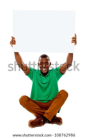 Seated young man holding white blank banner over his head - stock photo