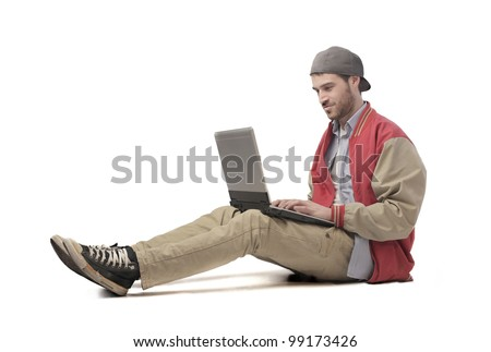 Seated young man using a laptop - stock photo