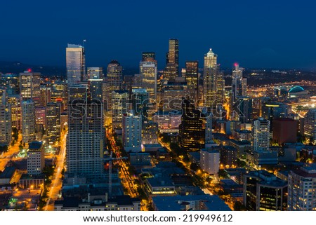 Seattle cityscape after sunset with city lights and blue sky. Mt. Rainier in the background. - stock photo
