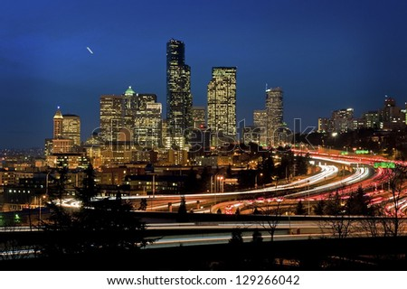 Seattle Commute. The Seattle, Washington skyline at night with Interstate 5 packed with cars and trucks during the commuter hours. - stock photo