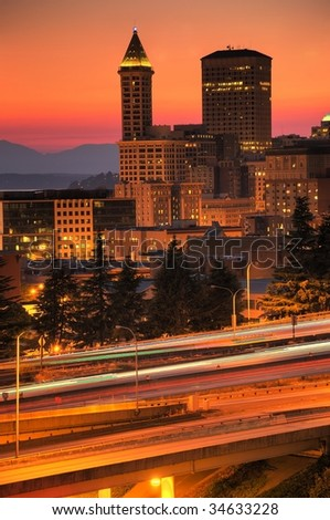 Seattle downtown buildings and Smith tower in the sunset glow with colorful streaks of traffic lights in the foreground freeways - stock photo