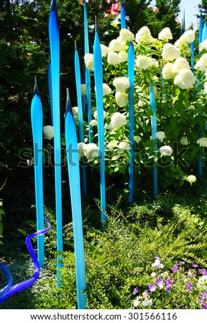 SEATTLE - JUL 23, 2015 - Blue blown glass tubes rise among hydrangeas in the  Chihuly Garden and Glass Museum,  Seattle, Washington - stock photo