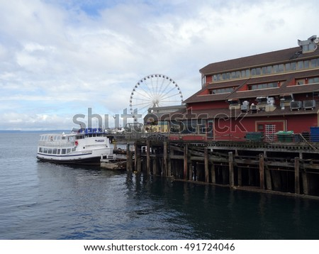 SEATTLE - JUNE 24, 2016: Argosy Boat parked at the Docks of the Pier District in Seattle, Washington with the Great Wheel in the Distance in Seattle during the summer on June 24, 2016.