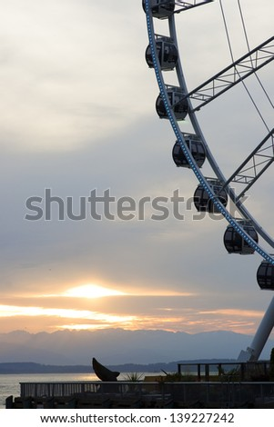SEATTLE, MAY 10: Seattle's Great Wheel is a giant Ferris Wheel turning on Pier 57 here over Puget Sound as the sun sets behind the Olympic Mountains May 10, 2013. - stock photo