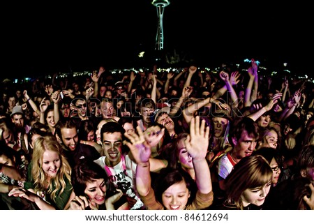 SEATTLE - SEPT. 3:  A large crowd of teenagers scream for their favorite band during the Bumbershoot Music Festival in front of the Space Needle in Seattle on September 3, 2011. - stock photo