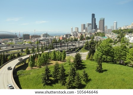 Seattle Skyline and Freeways. Downtown Seattle skyline with freeways foreground and Elliott Bay background. The mountains of the Olympic peninsula are visible in the distance. Washington State, USA. - stock photo