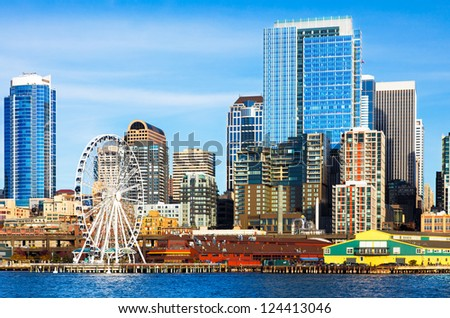 Seattle skyline and waterfront including the ferris wheel and sparkling high rise downtown buildings viewed from the bay on a bright clear day. - stock photo