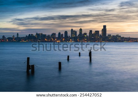 Seattle Sunrise. Sunrise over downtown Seattle with Elliott Bay and and old pilings in the foreground. Dramatic clouds add to the beauty of the landscape.