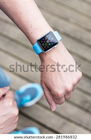 SEATTLE, USA - May 25, 2015: Man Using App on Apple Watch While Outside. Multiple Apps View.