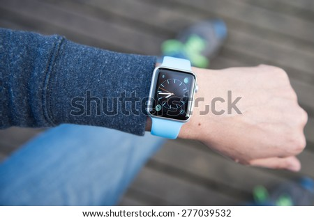 SEATTLE, USA - May 8, 2015: Man Using Watch App on Apple Watch to Check Time. - stock photo