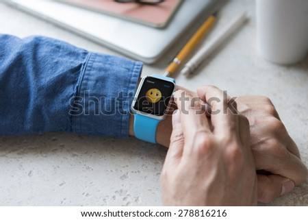 SEATTLE, USA - May 17, 2015: Man Wearing Sport Apple Watch with Blue Rubber Band. Happy Face Emoji Displayed. - stock photo