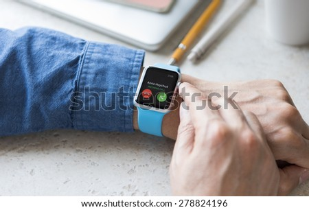SEATTLE, USA - May 17, 2015: Man Wearing Sport Apple Watch with Blue Rubber Band. Phone Call Incoming. - stock photo