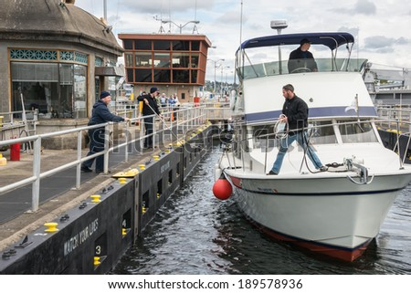SEATTLE, WA - APR 27, 2014: Outbound boat tying up in Hiram M. Chittenden Ballard Locks with help of Army Corps of Engineers in Seattle, Washington. - stock photo