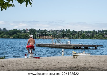 SEATTLE, WA - JULY 2, 2014:  Water Safety and Recreation: Lifeguard on duty on beach overlooking lake with swimming area and diving platform, Green Lake Park, Seattle Washington. - stock photo