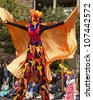 SEATTLE, WA - JUNE 16, 2012: A stilt walker in the Jaberwokey group with a golden cape and bird mask in the Fremont Summer Solstice parade to celebrate the start of summer in Seattle on June 16, 2012. - stock photo
