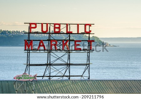 Seattle, WA, USA - July 6, 2014: Pike Place Market Neon Sign at Sunset. Pike Place Market is a farmers market. It was founded in 1907 to provide a place for customers to meet directly the producers. - stock photo