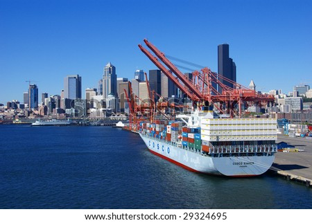SEATTLE, WASHINGTON - JUN 27: Dockyard cranes ready to lift containers from container vessel at Seattle waterfront Puget Sound, Pacific Northwest June 27, 2008 in Seattle. - stock photo