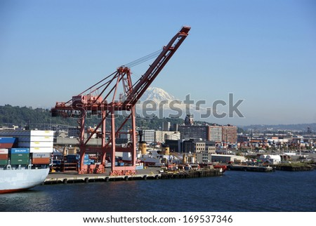 SEATTLE WASHINGTON 27 JUN 2008 - Dockyard cranes, Seattle waterfront with Mt Rainier in background,   Puget Sound,  Pacific Northwest - stock photo