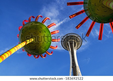 SEATTLE, WASHINGTON - NOVEMBER 23, 2013:  The landmark Space Needle soars overhead with two colorful flower sculptures. - stock photo